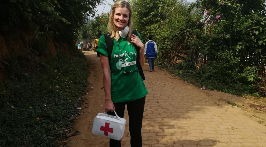 A female intern is pictured whilst distributing first aid kits to local schools during her public health internship in Madagascar.